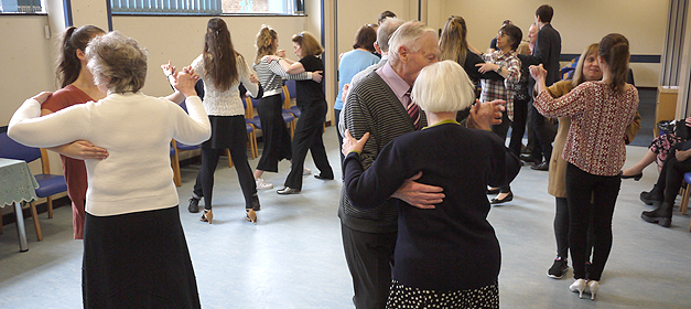 Blind and partially sighted clients dancing with volunteers at an SRSB client event