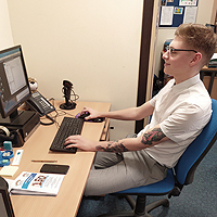 Photo of Taylor working at his desk
