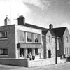 Black and white photograph of the front of Cairn Home showing the 1959 extension alongside the original 1935 building