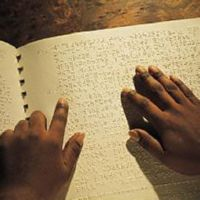 Photograph of 2 hands reading braille