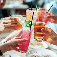 Photo of some peoples hands doing a cheers with glasses of drink