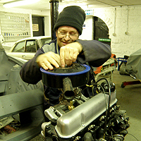Photograph of John working on an engine from a 1965 Ford Anglia
