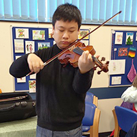 Photo of Zheyuan at SRSB playing violin