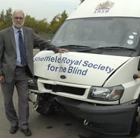 Photograph of damaged minibus with Steve Hambleton stood alongside looking very upset