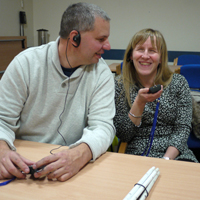 Photograph of clients using audio headsets