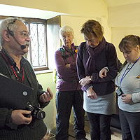 Photograph of people listening to audio descriotion at Bishops House