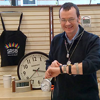 Photograph of Rob in Equipment Centre with lots of watches on his arm