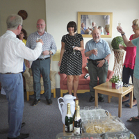 Photograph of group of trustees and staff toasting Kevin