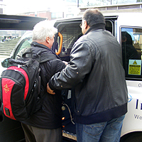 Photograph of a taxi driver assisting someone into a taxi