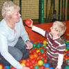 Photo of a young SRSB client playing in a ball pool