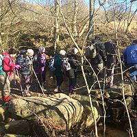 Photograph of walking group crossing a stream