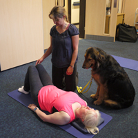 Photograph of someone doing pilates with instructor and guide dog