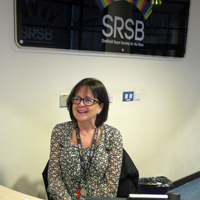 Photograph of Carol sat behind the reception desk