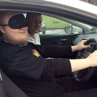 Photograph of driver at wheel with blindfold on