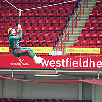 Photograph of a supporter taking part in a zip wire