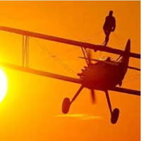 Photogrpah of someone standing on top of a plane doing a wing walk