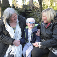 Photograph of one of SRSBs young clients with his mum and grandma