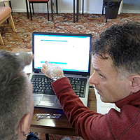 Photograph of volunteer with client on computer