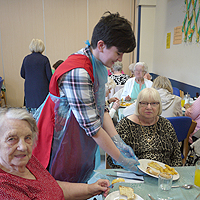 Photograph of a volunteer with clients in the activities centre