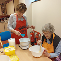 Photo of a volunteer with a client in one of the cookery groups